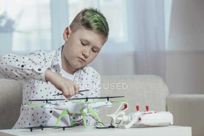 Drone réglage garçon confiant sur la table basse à la maison — Photo de stock