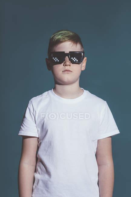 Garçon portant des lunettes de soleil pixel sur fond gris — Photo de stock