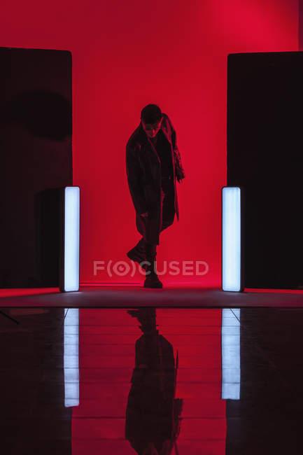 Junger Mann steht inmitten beleuchteter Lichter mit Reflex auf dem Boden in rotem Studio — Stockfoto