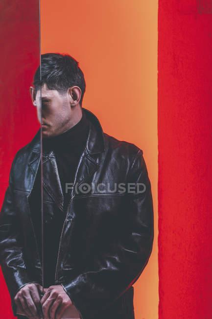 Giovane uomo di moda in piedi da specchio contro sfondo colorato — Foto stock