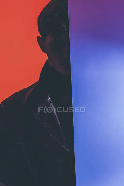 Молода людина стоїть за дзеркало проти оранжеве тло — стокове фото