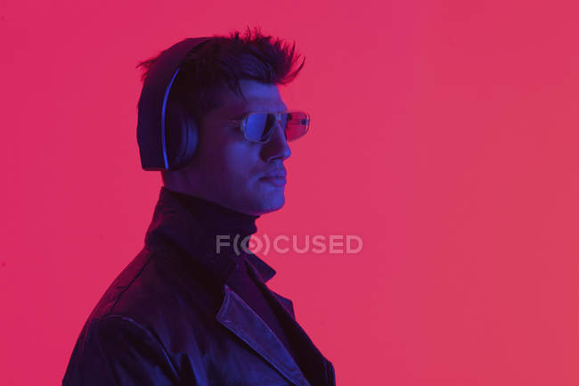 Young man wearing headphones and sunglasses against coral background — Stock Photo