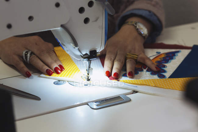 Cropped image of female designer's hand sewing textile on machine — Stock Photo