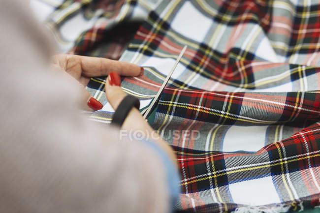 Ernte weibliche Beschneidung karierte Textil mit Schere — Stockfoto
