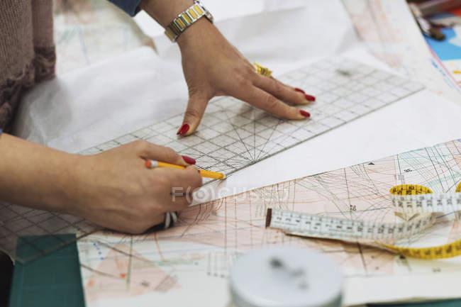 Cropped image of fashion designer marking on fabric at workshop — Stock Photo