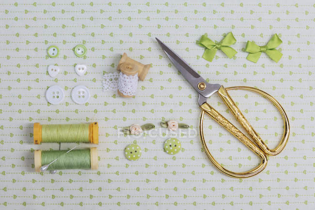 Directly above shot of various knitting equipment on green fabric — Stock Photo