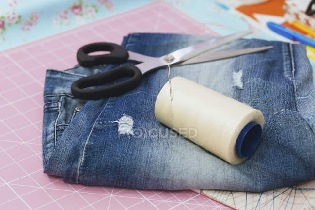 Still life of spool and scissors with jeans on cutting mat — Stock Photo
