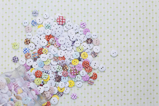 Directly above shot of multi colored various buttons on fabric — Stock Photo