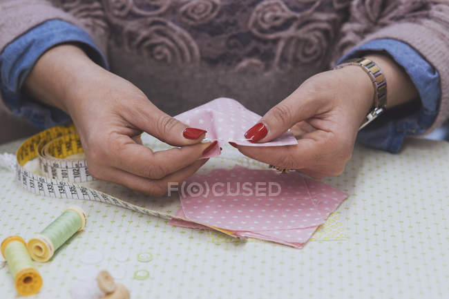 Midsection of fashion designer sewing pink fabrics — Stock Photo
