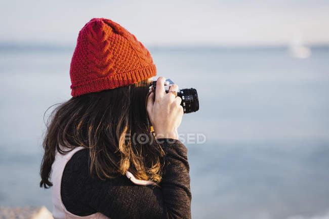 Вид збоку жінка фотографує проти моря — стокове фото
