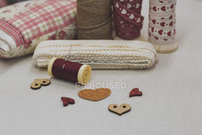 Различные кружева и катушки с сердцем форму кнопок на ткани — стоковое фото