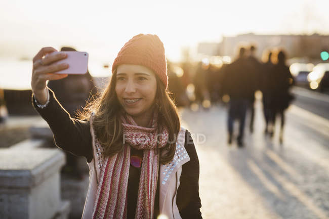 Smiling  woman taking selfie with smartphone during sunset — Stock Photo