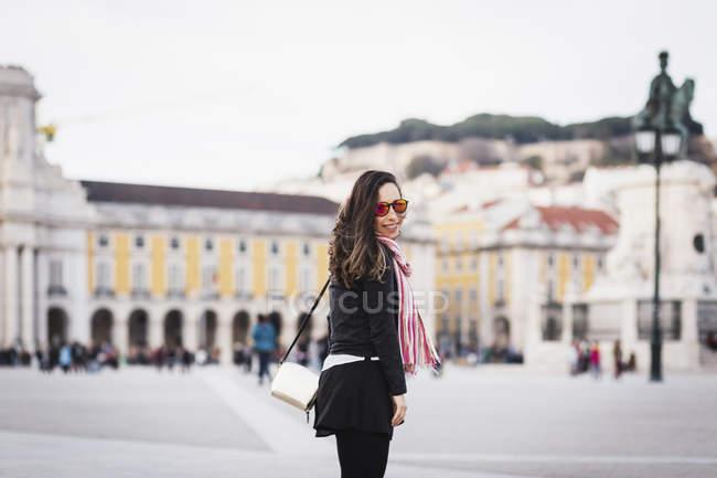 Улыбаясь середине взрослая женщина, стоя на Староместской площади и глядя через плечо на камеру — стоковое фото
