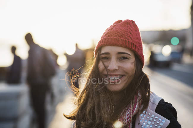 Portrait of smiling woman wearing knit hat looking at camera at street scene — Stock Photo