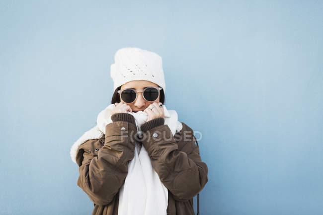 Menina em óculos de sol envolto em cachecol contra fundo azul — Fotografia de Stock