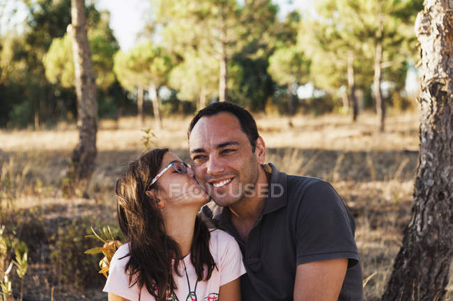 Girl kissing happy father sitting by tree trunk in forest — Stock Photo