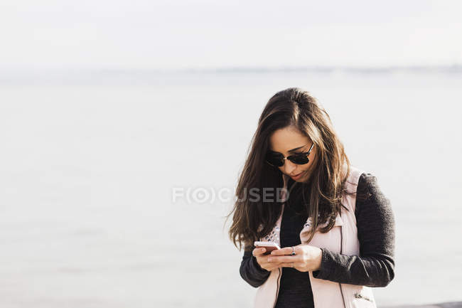 Woman browsing smartphone while standing against sea — Stock Photo