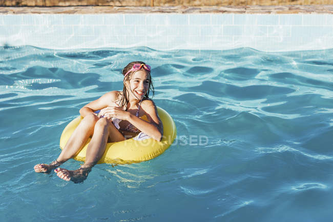 Полная длина счастливой девушки в надувном кольце на бассейне — стоковое фото
