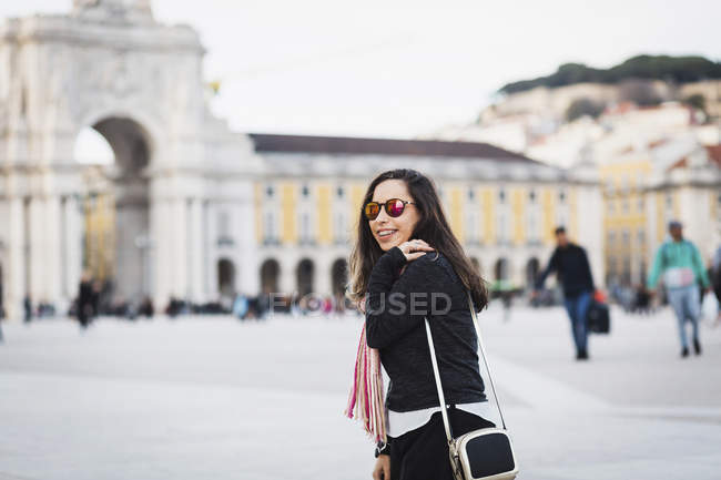 Smiling woman adjusting purse and  looking over shoulder at camera at town square — Stock Photo