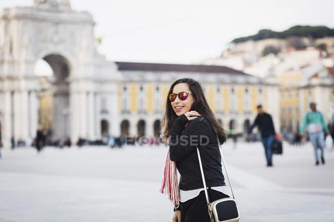 Ajuste bolsa de mulher a sorrir e a olhar por cima do ombro para câmera na Praça da cidade — Fotografia de Stock