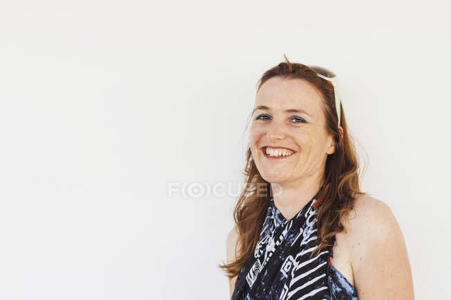 Portrait of cheerful woman wearing looking at camera against white background — Stock Photo
