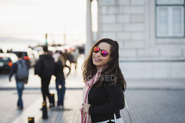 Улыбаясь середине взрослая женщина, стоя в городе и, глядя через плечо на камеру — стоковое фото