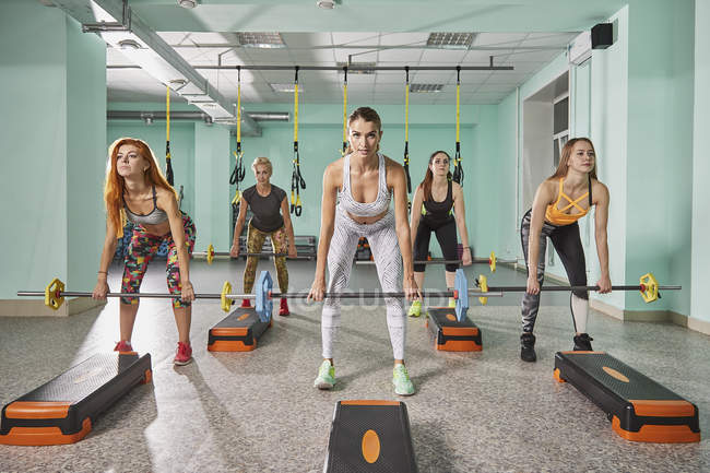 Full length of trainer with determined women lifting barbell during step aerobics — стоковое фото