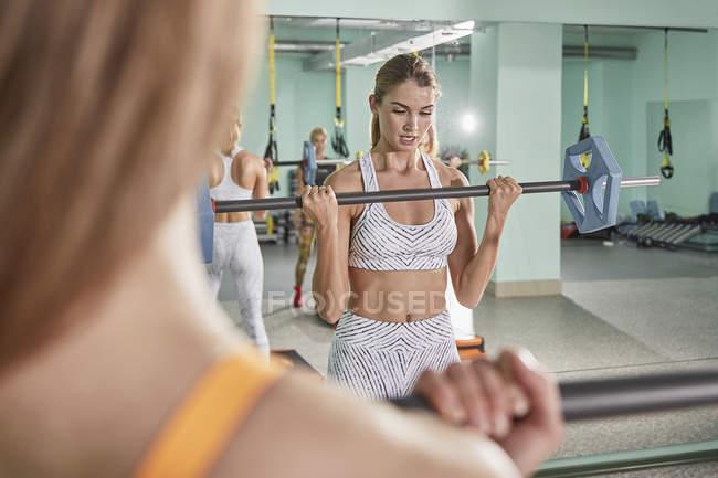 Определяется молодой женщины, осуществляющие со штангой в клубе здоровья — стоковое фото