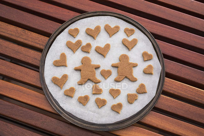 Gingerbread couple surrounded by hearts in baking sheet on table — Stock Photo