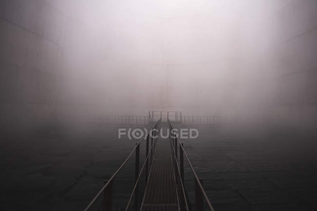Metallic walkway in misty light spot — Stock Photo