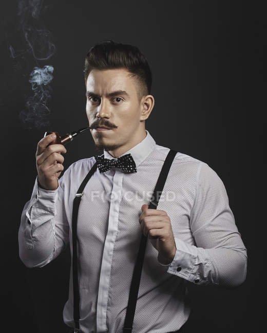 Portrait of confident young man wearing suspenders while smoking pipe over gray background — Stock Photo