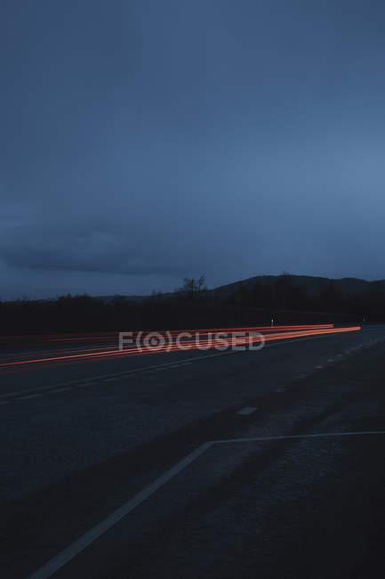 Trilhas de luz vermelha na estrada contra o céu à noite — Fotografia de Stock