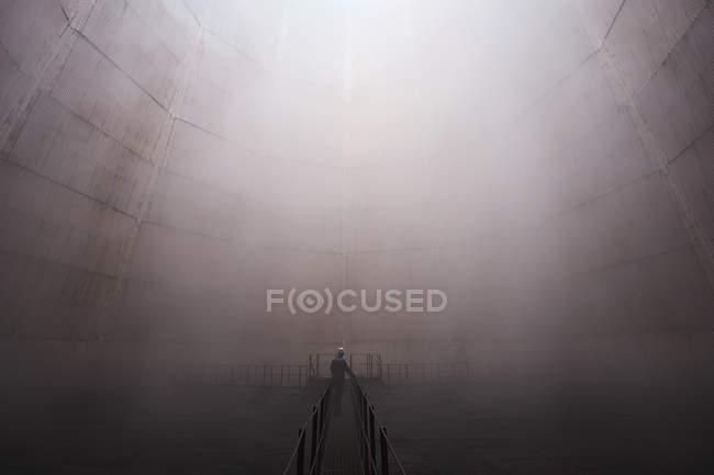 Uomo in piedi sulla passerella in tempo nebbioso — Foto stock