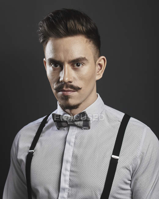 Portrait of confident young man wearing suspenders over gray background — Stock Photo
