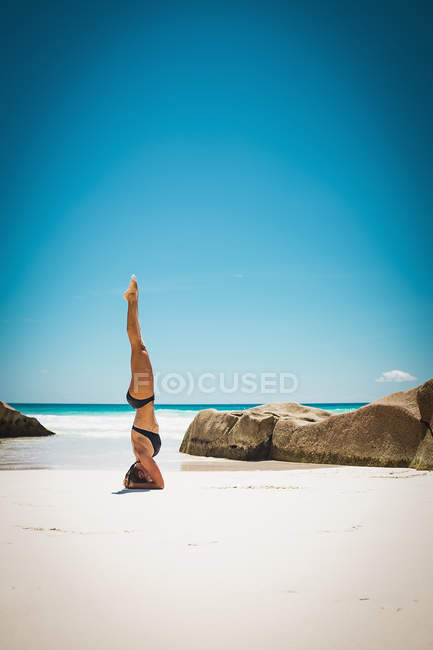 Side view of woman in bikini doing headstand at beach — Stock Photo