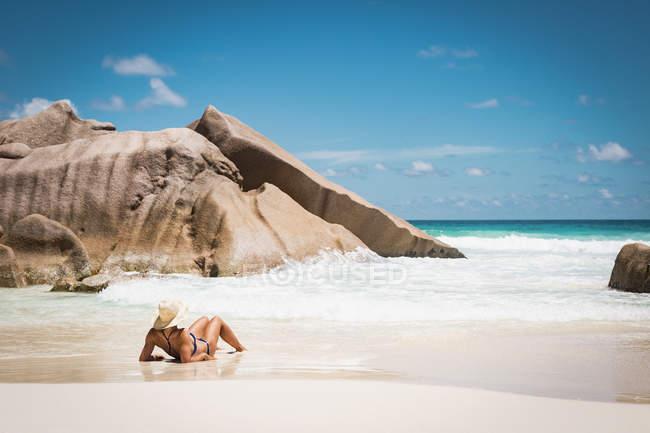Задній вид жінка в бікіні відпочинку на пляжі проти синього неба — стокове фото