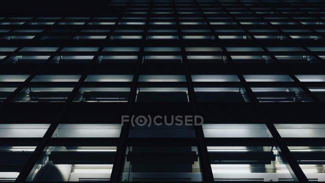 Vista de baixo ângulo da fachada do edifício de escritório à noite — Fotografia de Stock