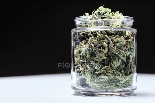 La marijuana ne laisse en pot de verre sur table sur fond noir — Photo de stock