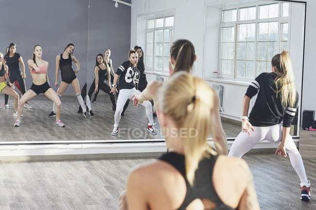 Dancers reflecting on mirror while dancing in rehearsals at studio — стоковое фото