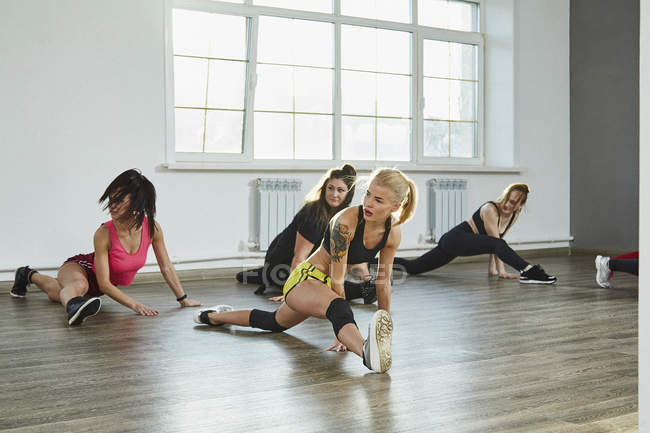 Confident young women practicing splits while dancing in studio — Stock Photo
