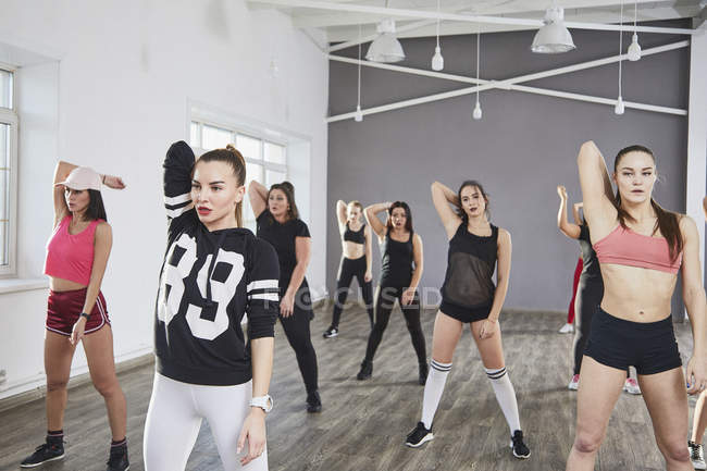 Confident women stretching hands while dancing in studio — стоковое фото