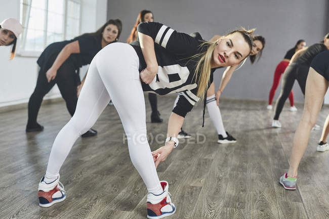 Confident young dancer dancing with friends in rehearsals at studio — Stock Photo