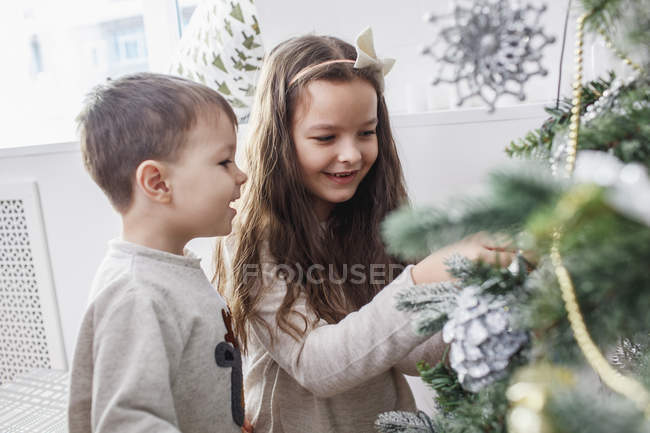 Happy siblings decorating Christmas tree at home — Stock Photo