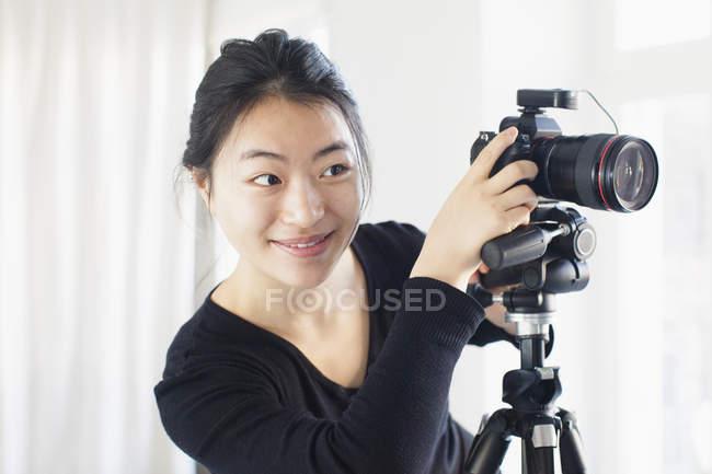 Lächelnde junge Frau mit Kamera fotografieren — Stockfoto
