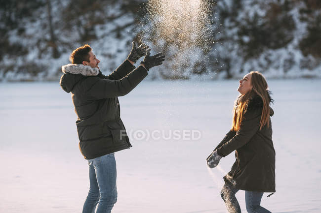 Side view of playful couple enjoying of throwing snow in air — Stock Photo