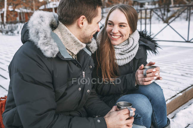 Happy couple sitting with drinks on boardwalk and looking at each other — Stock Photo