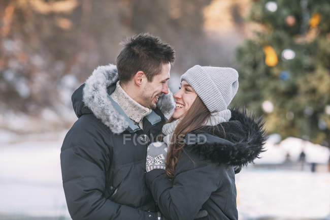 Smiling couple wearing warm clothing standing face to face — Stock Photo