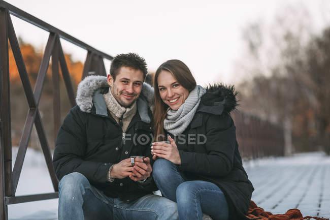 Porträt des Brautpaares sitzen mit Getränken am Boardwalk Winter tagsüber — Stockfoto