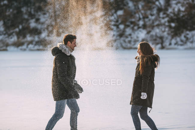 Вид сбоку играющих мужчины и женщины, бросающих снег — стоковое фото