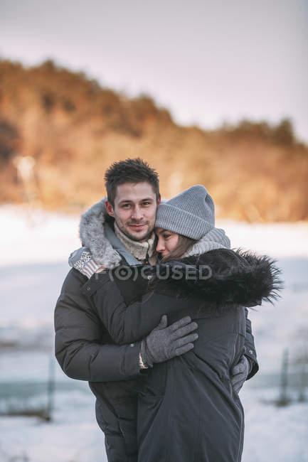 Porträt von Lächelnder Mann umarmt Frau Winter tagsüber — Stockfoto